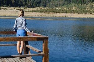 Full length of female hiker standing on pier