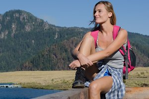 Full length of smiling female hiker sitting on railing at pier