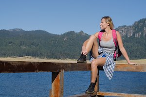 Smiling female hiker sitting on railing at pier