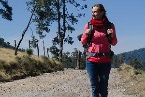 Full length of female hiker walking on dirt road