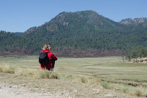 Rear view of female hiker with backpack sitting on field