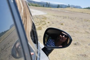 Close up of woman reflecting in side view mirror