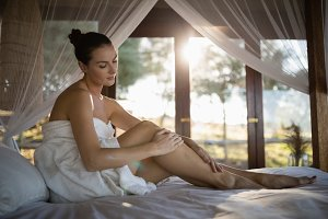 Woman applying lotion while sitting on canopy bed
