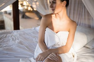 Woman in towel sitting on a canopy bed in cottage