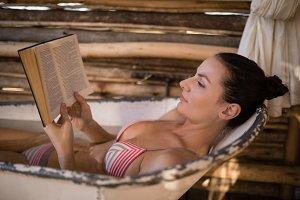 Woman reading a novel in bathtub