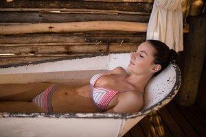 Woman sleeping in bathtub