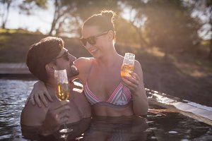 Couple having champagne in pool