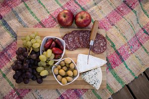 Fruits and salami on picnic blanket