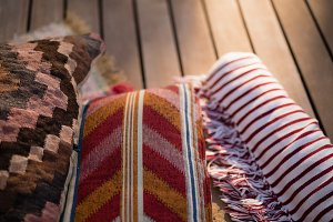 Cushions and picnic blanket on wooden plank