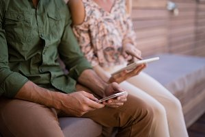 Couple using mobile phone and digital tablet during safari vacation