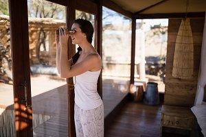 Beautiful woman looking through binoculars from window