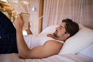 Man reading novel on canopy bed