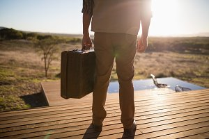 Low section of man with suitcase standing on wooden plank