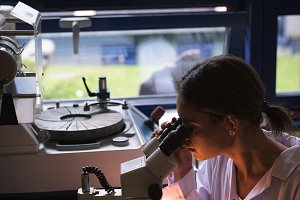 Female student using microscope in lab