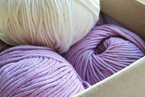 White and lilac yarn balls in a box.