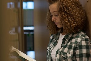 Female college student reading book while standing in library