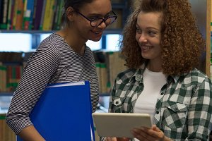 Smiling teenage girl showing tablet computer to friend