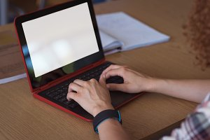 Cropped image of female university student using laptop