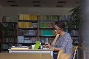 Female university student using digital tablet while sitting at desk