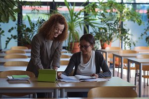 Smiling female students studying at desk