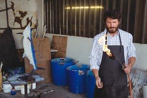Craftsman holding burner in workshop