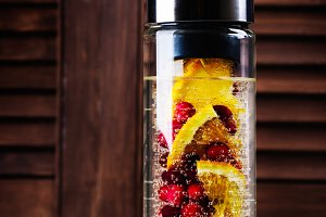 Infused water with cranberry and orange in a glass bottle