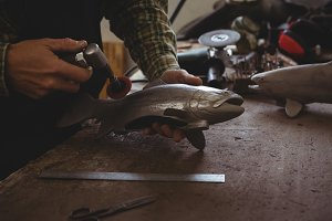Mid-section of craftsman shaping a metal fish