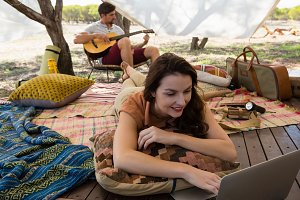 Woman using laptop with man playing guitar in tent