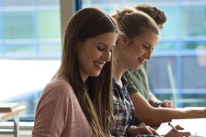 Side view of smiling students studying at desk