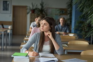 Thoughtful female college student at desk during exam