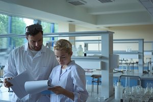 University students discussing reports in laboratory