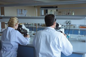 University students doing experiment on microscope in laboratory