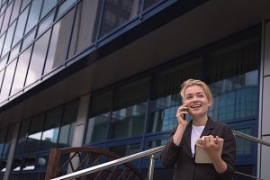 Smiling university student talking on mobile phone
