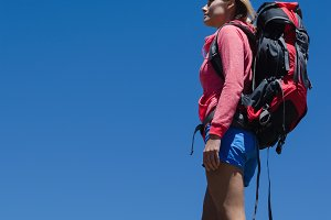 Low angle view of female hiker standing on rock
