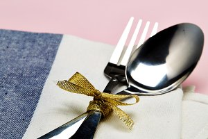 Set table with silver spoon and white napkin on pink with gray