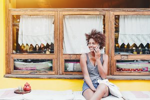 Black girl in street cafe with phone