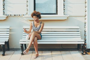 Black girl on bench with smartphone