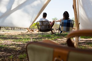 Rear view of couple on chairs outside tent