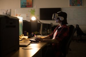 Executive using virtual reality headset while working at desk