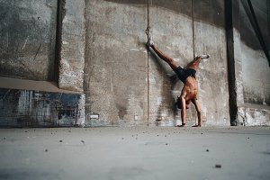 Fit man doing handstand split