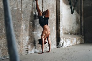 Fitness male model doing handstand