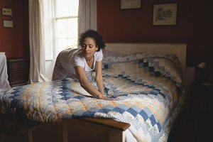 Woman making bed in bedroom