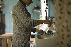 Woman washing a mug in the kitchen