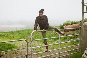 Woman crossing gate in field
