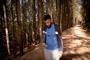 Man using phone while walking in forest