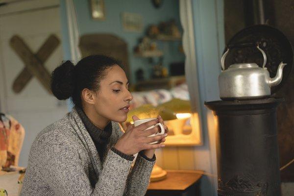 Thoughtful woman having coffee in k…