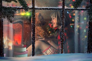 Looking through snowy window at home. Happy child with Teddy bear. Inside the house warm, fireplace. Happy Christmas