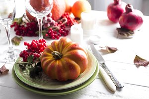 Thanksgiving dinner table setting with pumpkins,