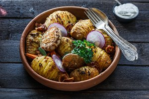 Oven-baked hassleback potatoes with onion and bacon