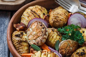 Bowl of oven roasted hassleback Potato with garlic, carrots and onion on rustic black wooden surface